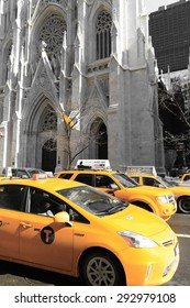 New York City, USA - March 6, 2015: Iconic yellow taxis outside St Patrick's Cathedral in Manhattan. St Patrick's Cathedral is a historic and popular place of worship.