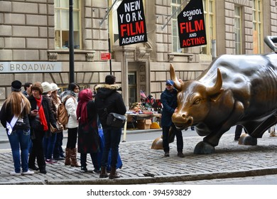 New York City, USA - March 19, 2016: Tourists taking picture with the Charging Bull statue on Broadway in Lower Manhattan in 2016 in New York City.