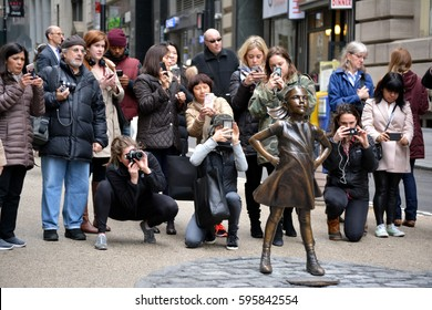 """New York City, USA - March 8, 2017: People taking pictures of """"The Fearless Girl"""" statue on International Women's Day near the Wall Street Bull in New York City."""