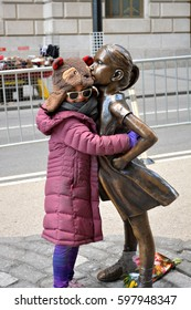 """New York City, USA - March 11, 2017: Young girl hugging """"The Fearless Girl"""" statue facing the Charging Bull in honor of International Women's Day in Lower Manhattan in New York City."""