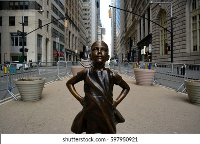 "New York City, USA - March 8, 2017: ""The Fearless Girl"" statue facing the Charging Bull erected to honor International Women's Day in Lower Manhattan in New York City."