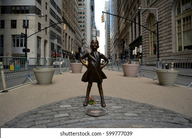 "New York City, USA - March 12, 2017: ""The Fearless Girl"" statue facing the Charging Bull in honor of International Women's Day in Lower Manhattan in New York City."