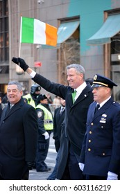 New York City, USA - March 17, 2017: New York City Mayor Bill de Blasio waving the flag of Ireland as he marches in the St. Patrick's Day Parade in Midtown Manhattan in New York City.