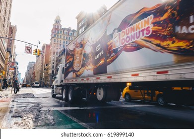 New York City, USA - March 20, 2017 : Dunkin' Donuts truck is crossing street at downtown Manhattan. Long exposure for motion blur.