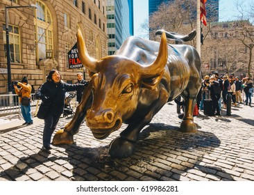 New York City, Usa - March 20, 2017: Tourists visits the Wall Street Charging Bull statue in Wall Street. Is symbol of aggressive financial optimism and prosperity.