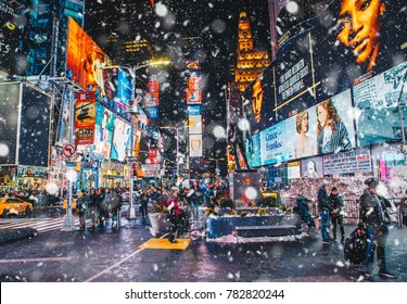 New York City, USA - March 18, 2017: People and famous led advertising panels in Times Square during snow, one of the  symbol of New York City.