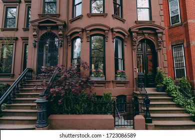 New York City, New York / USA - May 5 2020: Brooklyn brownstone houses and facades. Brooklyn buildings with windows and green trees.