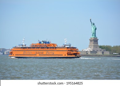 NEW YORK CITY, USA - May 26, 2014: Staten Island Ferry passing the Statue of Liberty in  New York Harbor.