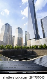 NEW YORK CITY, USA - MAY 30, 2013: Ground level view of the 9/11 memorial which includes one of the two waterfalls and names of the victims in the foreground, and new towers behind.