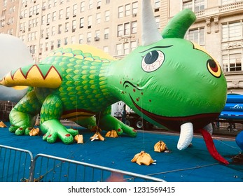 New York City, New York, USA- November 22, 2017:Rex the Happy Dragon is secured with weights during the balloon inflation in preparation for the annual Macy's Thanksgiving Day Parade.