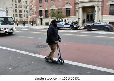 New York City, USA - November 12, 2018: A man rides an electric scooter or e-scooter along a midtown Manhattan street.