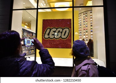 New York City, USA - November 12, 2018: Tourists take a picture of a Lego store in Manhattan.