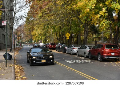 New York City, USA - November 12, 2018: Traffic drives along a tree lined residential street in Queens on a sunny autumn day. The warm weather has resulted in a spectacular display of fall colours.