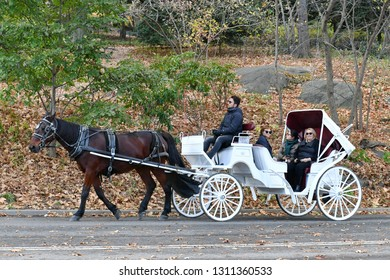 New York City, USA - November 16, 2017: Tourists ride a traditional ornate horse drawn carriage through Manhattan's Central Park.