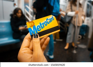New York City, USA. November 2019: Hand holding a MetroCard in New York City. Metrocard allows you to travel on New York City public transport.. Teal and orange style