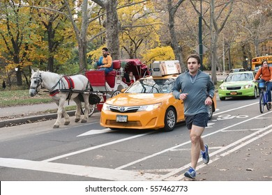 New York City, USA - November 16, 2016: Pedestrians and traffic pass through Central Park. The park is the most visited urban park in the United States with 40 million visitors a year.
