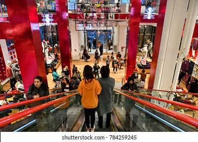 New York City, USA - November 16, 2017: Shoppers descend an escalator in a Uniqlo store in Manhattan. The Japanese causal wear designer and manufacturer is a subsidiary of Fast Retailing Company.