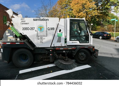 New York City, USA - November 16, 2017: A street sweeper vehicle cleans a road in the Kew Gardens borough of Queens. The NYC Department of Sanitation is responsible for cleaning the city's streets.