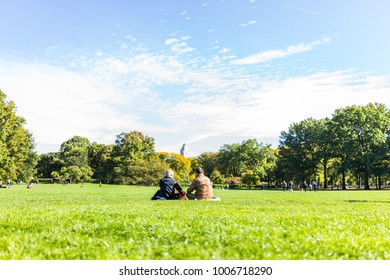 New York City, USA - October 28, 2017: Manhattan NYC Central park with couple people sitting having picnic in front of buildings skyscrapers view on great lawn grass meadow in autumn fall season