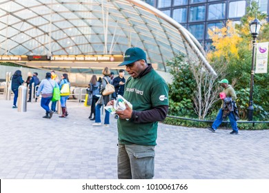 New York City, USA - October 27, 2017: Man handing out Fresh&Co smartwater flyers by urban in NYC Chelsea West Side 34th Street Hudson Yards Subway Station
