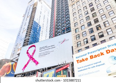 New York City, USA - October 28, 2017: Manhattan NYC buildings of midtown Times Square, Broadway avenue road, signs ads for pink ribbon breast cancer campaign, dea, national prescription drug