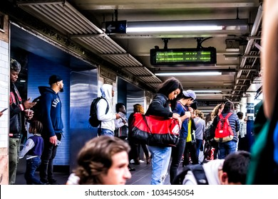 New York City, USA - October 28, 2017: People waiting in underground transit empty large platform in NYC Subway Station in downtown, looking at phones on Fulton street