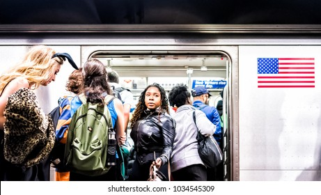 New York City, USA - October 28, 2017: People in underground platform transit in NYC Subway Station on commute with train, people crammed crowd with open closing doors, woman exiting, boarding
