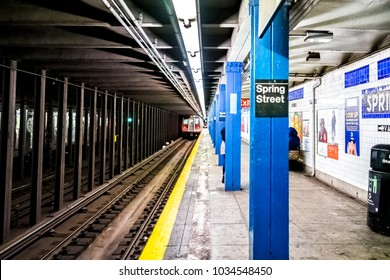 New York City, USA - October 28, 2017: People waiting in underground transit empty large platform in NYC Subway Station, Spring street sign in downtown, train approaching, arriving