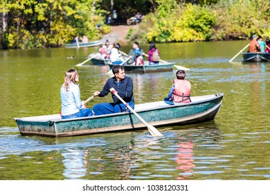 New York City, USA - October 28, 2017: Central Park in Manhattan, New York City nyc by The Lake during sunny autumn day with people rowing on romantic boats, gondolas in water