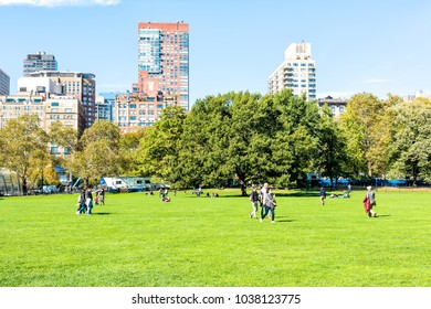 New York City, USA - October 28, 2017: Manhattan NYC Central park Great Lawn with people walking on green grass meadow in autumn fall season, buildings cityscape skyline