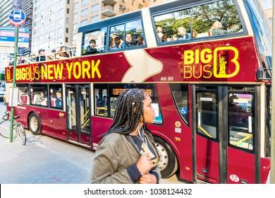 New York City, USA - October 28, 2017: Manhattan NYC midtown Columbus Circle, Broadway street road, Big bus bigbus, young woman walking by red double decker