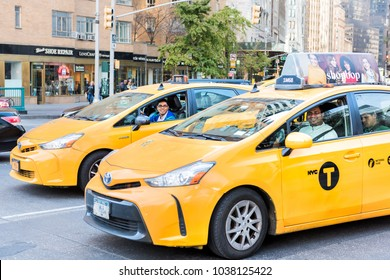 New York City, USA - October 28, 2017: Midtown Manhattan with intersection of Columbus Circle and Broadway street road with many yellow taxi cab cars in traffic, happy indian asian men drivers