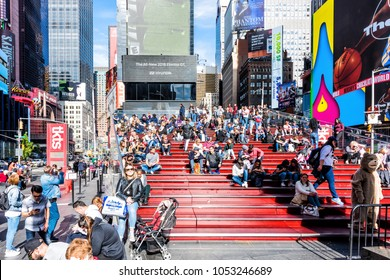 New York City, USA - October 28, 2017: Manhattan NYC buildings of midtown Times Square, Broadway avenue road, Duffy Square with many crowd people sitting on benches bleachers stairs