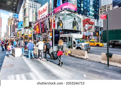 New York City, USA - October 28, 2017: Manhattan NYC buildings of midtown Times Square, Broadway avenue road, signs ads, many large huge crowd of people crowded walking on street outside