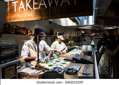 New York City, USA - October 30, 2017: Man chef cutting foccacia bread pizza baked in oven in Rana restaurant kitchen in Chelsea Market