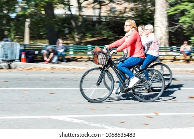 New York City, USA - October 28, 2017: Midtown Manhattan with closeup panning shot of one single woman riding bicycle bike basket in Central Park road in traffic on sunny day NYC