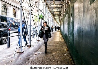 New York City, USA - October 30, 2017: People walking on Broadway St by Wall Street under cover scaffold construction in NYC Manhattan lower financial district downtown, NYSE
