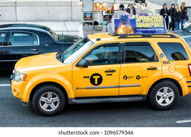 New York City, USA - October 30, 2017: Midtown Manhattan NYC NY with street road, yellow taxi cab cars in traffic, Spongebob Squarepants musical ad
