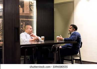 New York City, USA - October 30, 2017: Inside Starbucks store in midtown Manhattan NYC NY with people work colleagues talking over food, coffee in cafe sitting at table