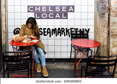 New York City, USA - October 30, 2017: Market food shop food court in Chelsea neighborhood district Manhattan NYC, woman sitting at table with local sign