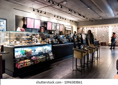 New York City, USA - October 30, 2017: Inside Starbucks store in midtown Manhattan NYC NY with people walking, menu, order counter selection of food, coffee in cafe
