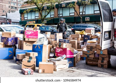 New York City, USA - October 30, 2017: Delivery man with many boxes in NYC by BH photo video store, van truck unloading amazon prime, walmart, chewy, blue apron