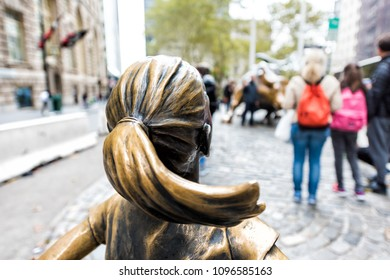New York City, USA - October 30, 2017: Wall Street stock exchange The Fearless Girl statue facing Charging Bull metal in NYC Manhattan lower financial district downtown, bokeh closeup NYSE