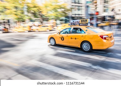 New York City, USA - October 28, 2017: Midtown Manhattan Columbus Circle and Broadway street road with panning shot of one single yellow taxi cab car in motion