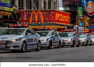 New York City, USA - October 7 2014: Row of NYPD cars travelling past McDonalds in Time Square, New York City