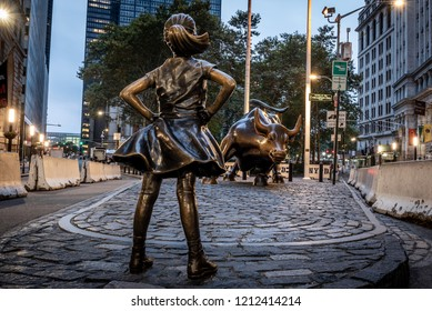 NEW YORK CITY, USA - OCTOBER 11, 2018: The Fearless Girl facing the Charging Bull statue at dawn, located in lower Manhattan on Wall Street