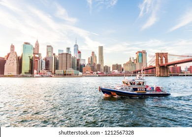 New York City, USA - October 28, 2017: Outdoors view in NYC New York City Brooklyn Bridge Park by east river, cityscape skyline, skyscrapers, sunset, NYPD, police department coastal guard boat, ship