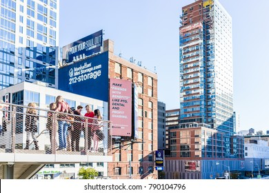 New York City, USA - October 27, 2017: Modern glass skyscrapers apartment buildings in NYC in Chelsea West Side by Hudson Yards, with people standing on high line park, taking photos, pictures, selfie
