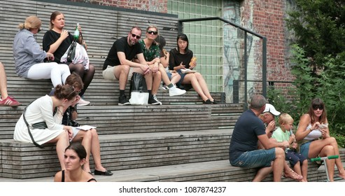 NEW YORK CITY, USA - September 20, 2017- HIGH LINE PARK IN NYC. People sitting on park benches enjoying metropolitan city attraction. Multi-cultural diverse people sitting and relaxing outdoors