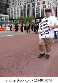 """New York City, New York / USA - September 08 2018: During the New York City Labor Day Parade, marchers carry signs highlighting issues such as """"Unfair Trade Policies"""" and the """"Corporate Agenda""""."""